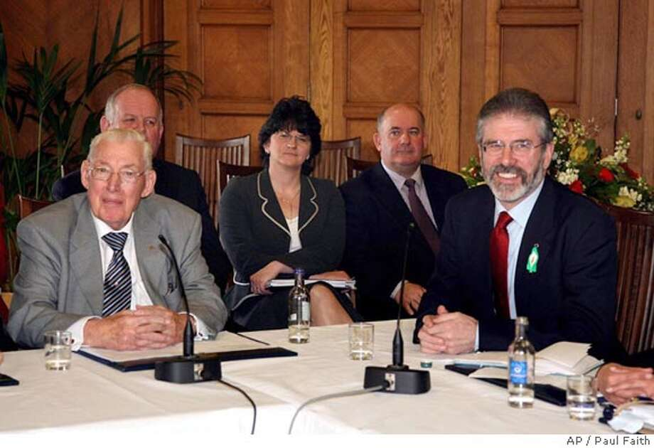 Democratic Unionist Party leader Ian Paisley, left, and Sinn Fein President Gerry Adams speak to the media during a press conference at the Stormont Assembly building in Belfast, Northern Ireland, Monday March 26, 2007. Sitting side by side for the first time in history, the leaders of Northern Ireland's major Protestant and Catholic parties announced a stunning deal Monday to forge a power-sharing administration May 8. The breakthrough followed unprecedented face-to-face negotiations between the Protestants of Ian Paisley's Democratic Unionist Party and the Catholics of Gerry Adams' Sinn Fein. The two foes, who previously negotiated only via third parties, sat beside each other at a table in the main dining room in Stormont Parliamentary Building in Belfast but reportedly did not shake hands. (AP Photo/Paul Faith/pool) Photo: Paul Faith