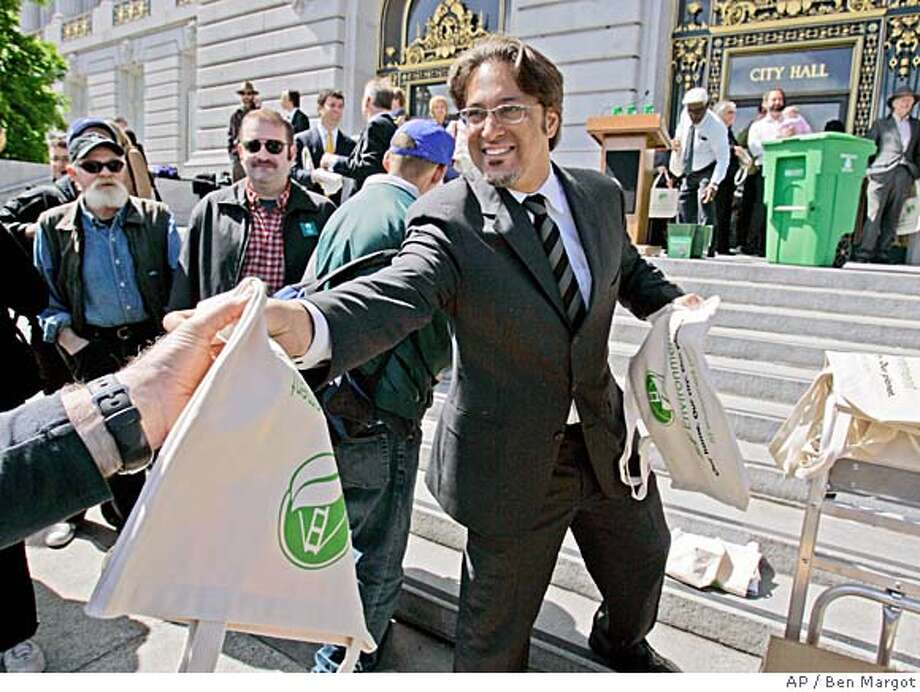 San Francisco Supervisor Ross Mirkarimi hands out canvas shopping bags, Tuesday, March 27, 2007, in San Francisco. San Francisco's Board of Supervisors on Tuesday is to consider passing an ordinance that would require large supermarkets and pharmacies in the city to replace non-biodegradable plastic bags with reusable or recyclable bags, a move that would make San Francisco the first city in the U.S. to introduce such a ban. Mirkarimi, who sponsored the original version of the ordinance, said the proposal has the support of most supervisors, the city's garbage disposal contractor, and even many smaller retailers, who won't have to comply with the ban. (AP Photo/Ben Margot) Photo: Ben Margot