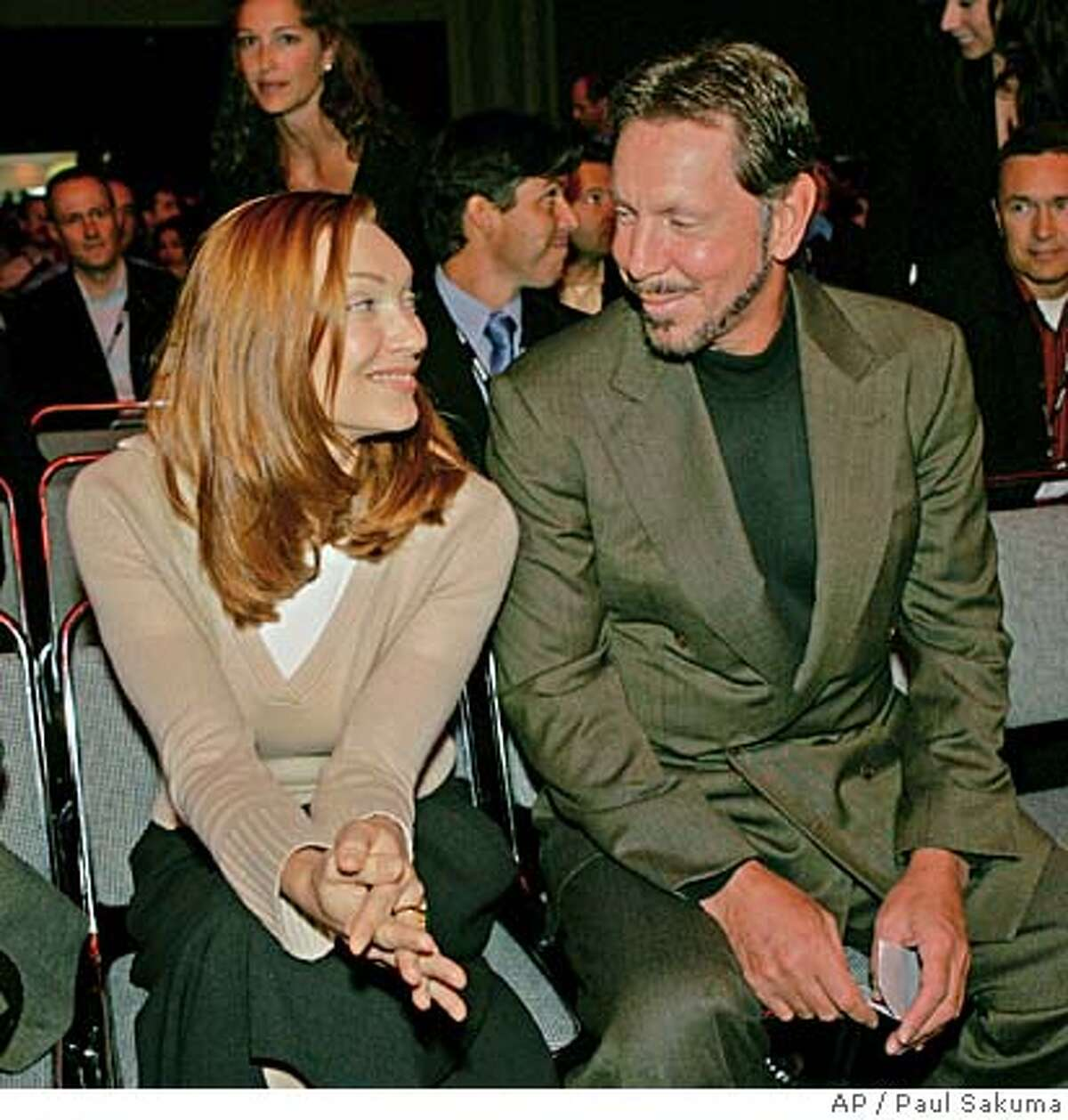 Oracle chief executive Larry Ellison smiles at his wife, Melanie Ellison, before he gave a keynote address at the Oracle Open World Conference in San Francisco, Wednesday, Sept. 21, 2005. (AP Photo/Paul Sakuma)