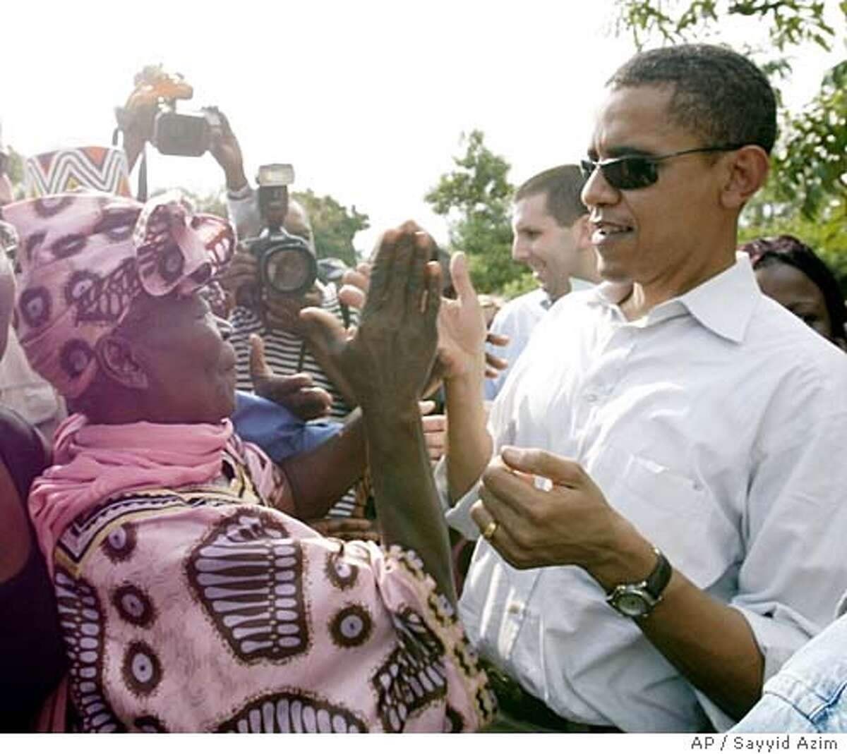 ** ATTN MARK- RETRANSMISSION OF ORIGINAL FILE** U.S. Senator Barack Obama, right, claps hands with his grandmother Sarah Hussein Obama at his father's house in Nyongoma Kogelo village, western Kenya, Saturday, Aug. 26, 2006. (AP Photo/Sayyid Azim)