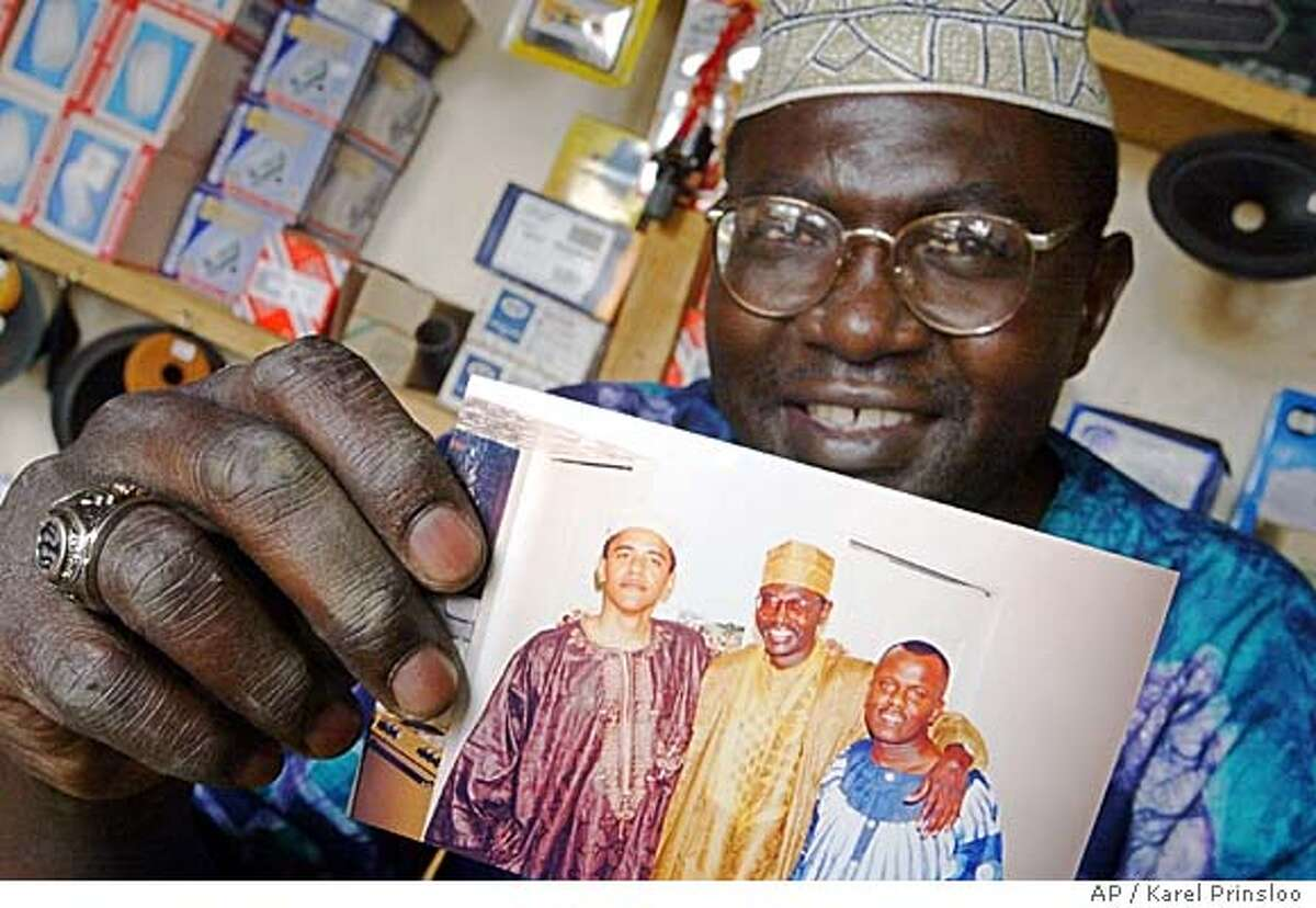 Malik Obama, the older brother of Barack Obama, holds an undated photo of Barack, Malik and an unidentified friend while sitting in his Siaya, Kenya, shop. Associated Press photo by Karel Prinsloo