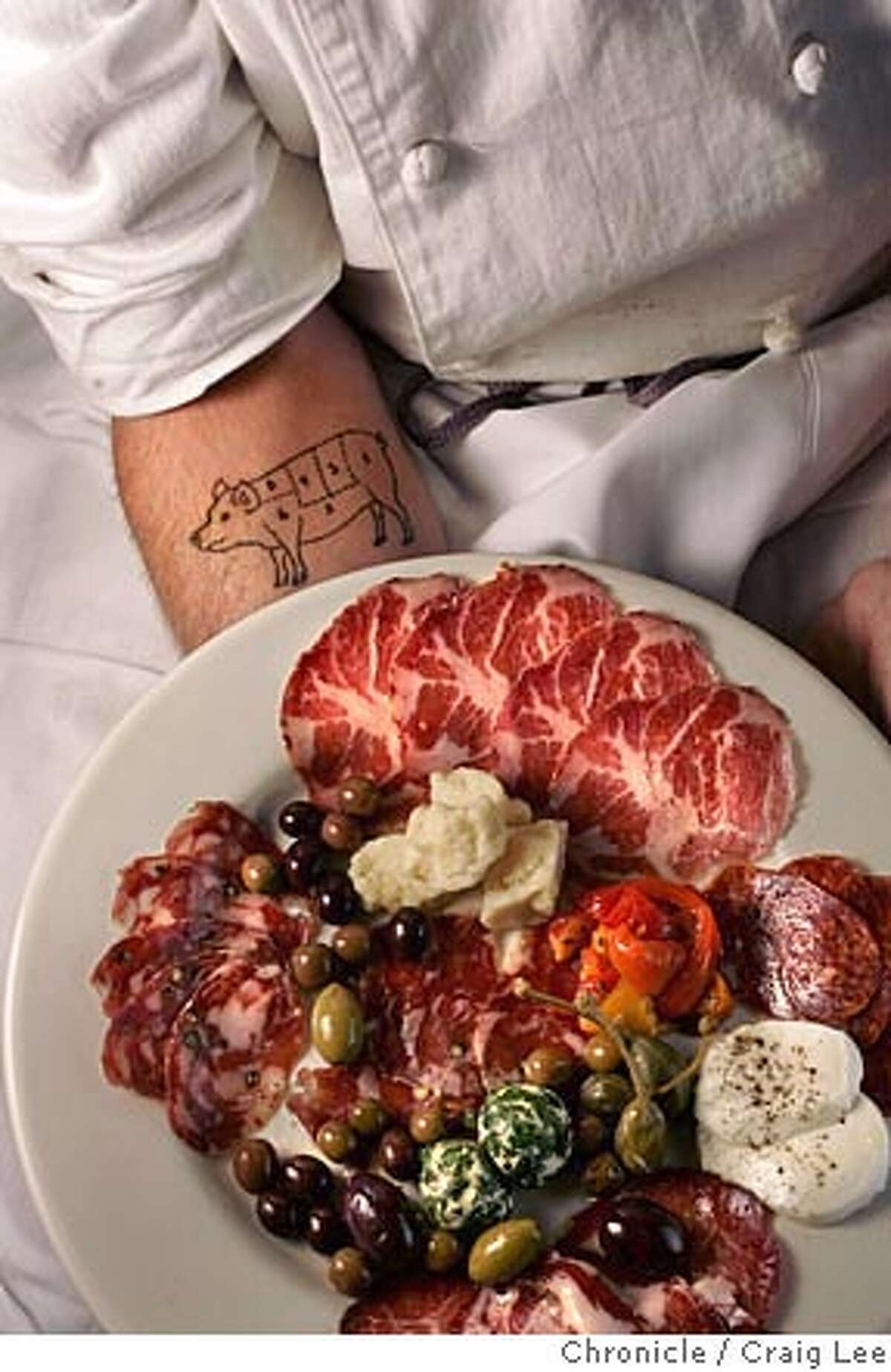 John Stewart, a chef who makes salumi and serves it at his restaurants, Bovolo in Healdsburg and Zazu in Santa Rosa. The photo was taken at his Bovolo restaurant. Photo of his tattoo of a pig on his arm and a plate of his salumi. Event on 8/26/05 in Healdsburg. Craig Lee / The Chronicle