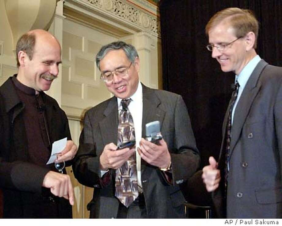 Paul Liao, President of Panasonic Technologies Company and Chief Technology Officer of Matsushita, center, shows off home movies of his grandson on his Palm that was transferred from his digital camera, to Paul Saffo, left, Director of the Institute for the Future, and Chris Pedersen, right, Director of Consumer Strategy of Hewlett Packard Company, during the launch of the Digital Home Working Group (DHWG) in San Francisco, Tuesday, June 24, 2003. In the latest effort to simplify , 17 leading high-tech companies formed a working group Tuesday to forge guidelines so that music players, televisions, computers, video cameras and other devices will interoperate.. (AP Photo/Paul Sakuma) Photo: PAUL SAKUMA