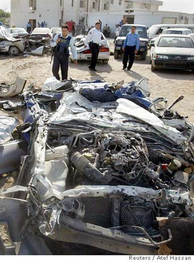 Police look at vehicles crushed by a tracked vehicle after a British raid on a jail in the southern Iraqi city of Basra September 20, 2005. An Iraqi Interior Ministry official said that British forces stormed the Major Crimes Unit Monday night using six tanks and freed two British undercover soldiers who had been arrested earlier in the day. REUTERS/Atef Hassan Photo: ATEF HASSAN
