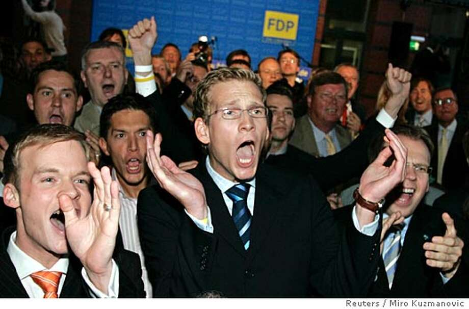 Free Democratic Party party members celebrate after watching the first results of the German election at the headquater of the FDP in Berlin September 18, 2005. Angela Merkel's conservatives were the leading party in Sunday's German election but her centre-right alliance lacked a parliamentary majority, exit polls indicated as voting ended. REUTERS/Miro Kuzmanovic Photo: MIRO KUZMANOVIC