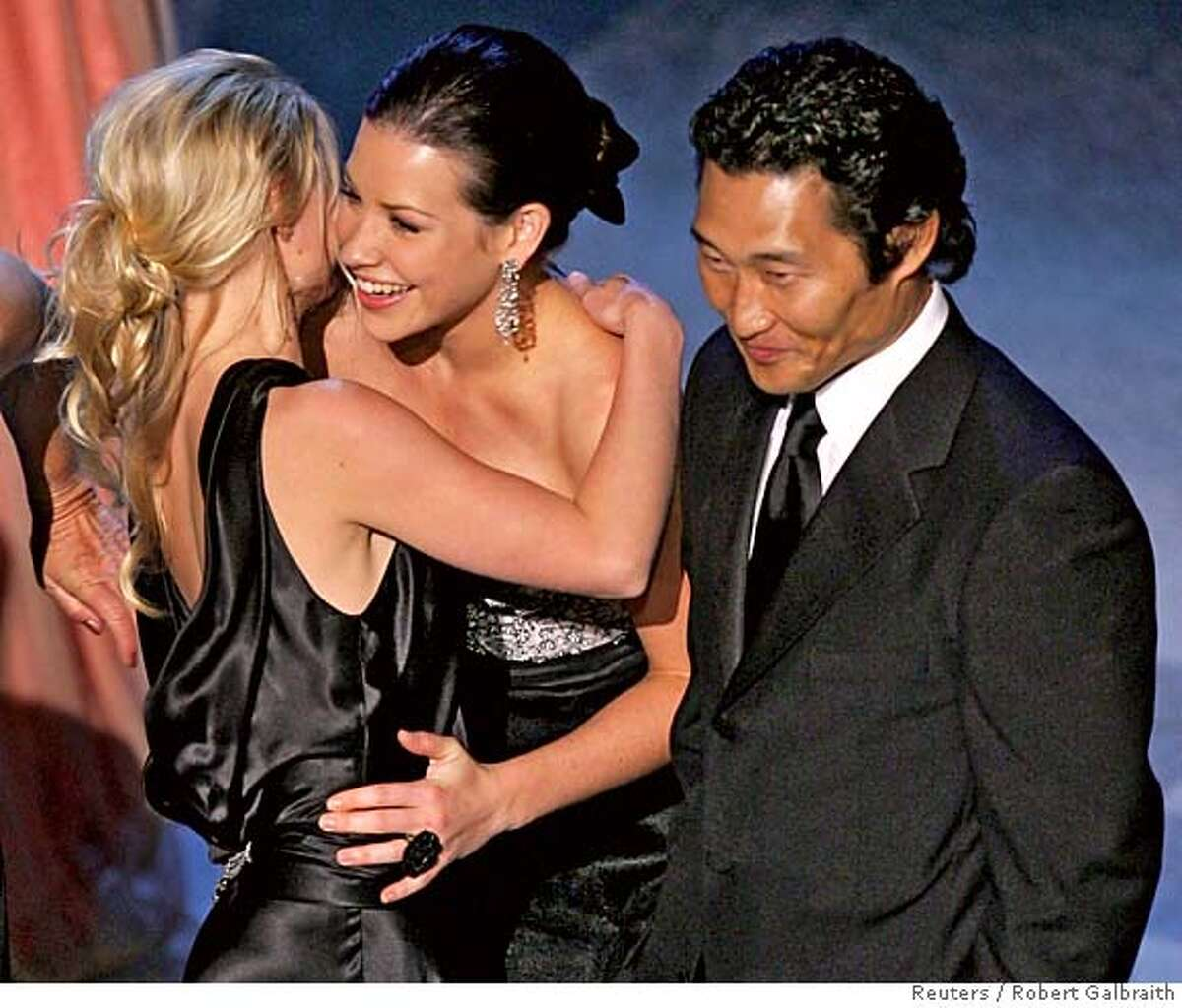 """Cast members of the television program """"Lost"""" (L-R) Emilie de Ravin, Evangeline Lilly and Daniel Dae Kim celebrate at the 57th annual Primetime Emmy Awards at the Shrine Auditorium in Los Angeles September 18, 2005. The show won an Emmy for best Drama Series. REUTERS/Robert Galbraith 0"""