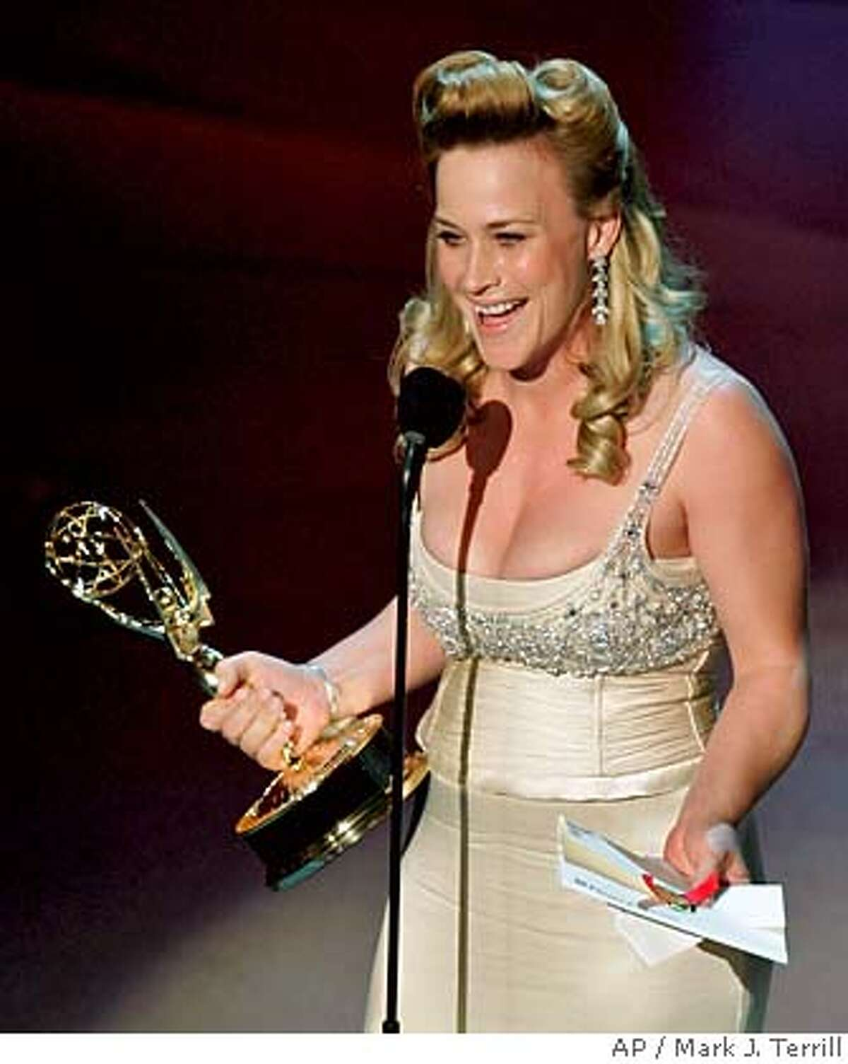 """Patricia Arquette accepts the award for outstanding lead actress in a drama series for her work on """"Medium"""" at the 57th Annual Primetime Emmy Awards Sunday, Sept. 18, 2005, in Los Angeles. (AP Photo/Mark J. Terrill)"""