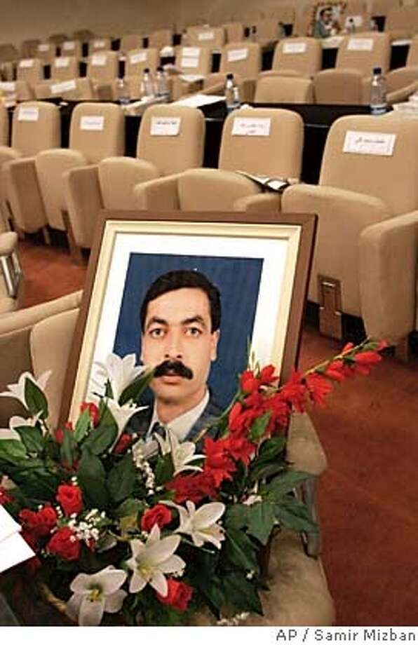 "The picture of Faris Nasir Hussein, a member of the Patriotic Union of Kurdistan party who was killed in an ambush late Saturday about 80 kilometers (50 miles) north of Baghdad, is seen on his chair before the National Assembly session in the Iraqi capital Sunday Sept. 18, 2005. ""The terrorists have launched a war of aggression against all Iraqis (but) we are up to it,"" Hussain al-Shahristani, the National Assembly's deputy speaker, unseen, said Sunday. (AP Photo/Samir Mizban) POOL Photo: SAMIR MIZBAN"
