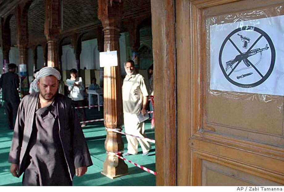 An Afghan voter walks out of a polling station past a sign banning weapons after he casted his ballot for the parliamentry elections in Afghan capital of Kabul Sunday, Sept. 18, 2005. Afghans choose a legislature for the first time in decades, embracing their newly recovered democratic rights and braving threats of Taliban attacks to cast votes in schools, tents and mosques.(AP Photo/Xinhua, Zabi Tamanna) Photo: ZABI TAMANNA