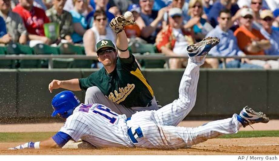 Oakland Athletics third baseman Donnie Murphy can't handle a throw as Chicago Cubs' Aramis Ramirez slides into third for a triple during the first inning of a spring training baseball game, Wednesday, March 7, 2007, in Mesa, Ariz. (AP Photo/Morry Gash) Photo: Morry Gash