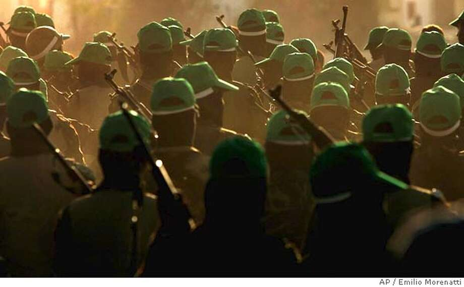 Masked Palestinian militants of Hamas march during a rally celebrating the Israeli withdrawal from Gaza in the evacuated Jewish settlement of Neve Dekalim, in the southern Gaza Strip, Friday, Sept. 16, 2005. (AP Photo/Emilio Morenatti) Ran on: 09-17-2005  Members of Hamas, a Palestinian militant group, march through a former Jewish settlement in Gaza. Ran on: 09-17-2005 Photo: EMILIO MORENATTI