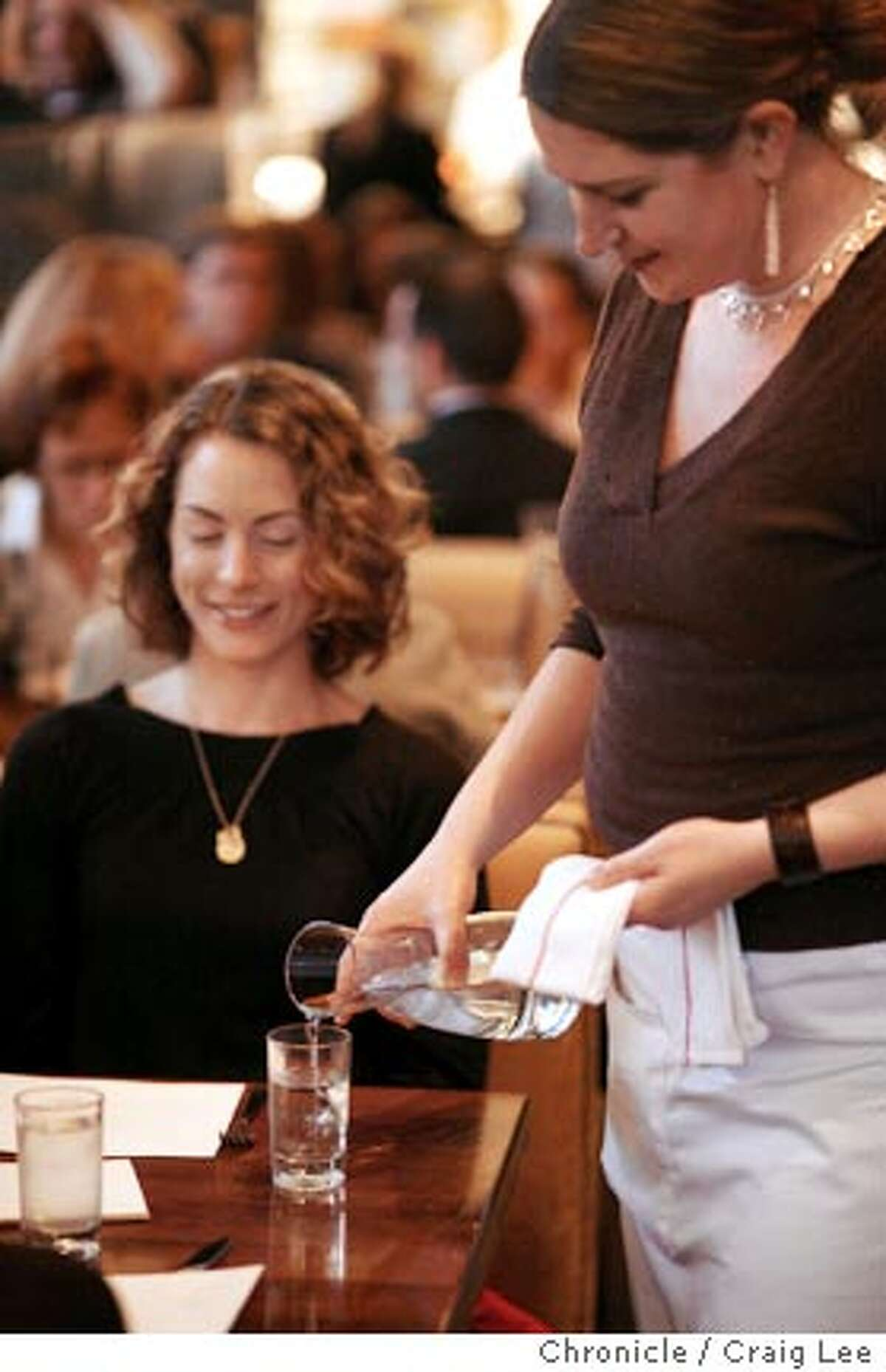 WATERSUPPLY_351_cl.JPG FOR THE FOOD SUPPLY column kickoff, the story is about some restaurants that have stopped serving bottled water for sustainability reasons. This photo is at Nopa restaurant in San Francisco. Waitress, Jennifer Skiman, serving dining customer, Kristina Campbell from SF, some filtered water. Event on 3/14/07 in San Francisco. photo by Craig Lee / The Chronicle MANDATORY CREDIT FOR PHOTOG AND SF CHRONICLE/NO SALES-MAGS OUT