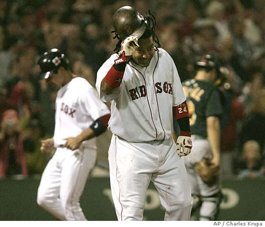 Boston Red Sox Manny Ramirez, center, smiles as he takes his helmet off after being hit by a pitch with bases loaded in the bottom of the 10th inning of Oakland Athletics pitcher Keiichi Yabu at Fenway Park in Boston, Friday, Sept. 16, 2005. The Red Sox won, 3-2. In background are Oakland catcher Jason Kendall, right, and scoring is pinch runner Alejandro Machado, left. (AP Photo/Charles Krupa) Photo: CHARLES KRUPA