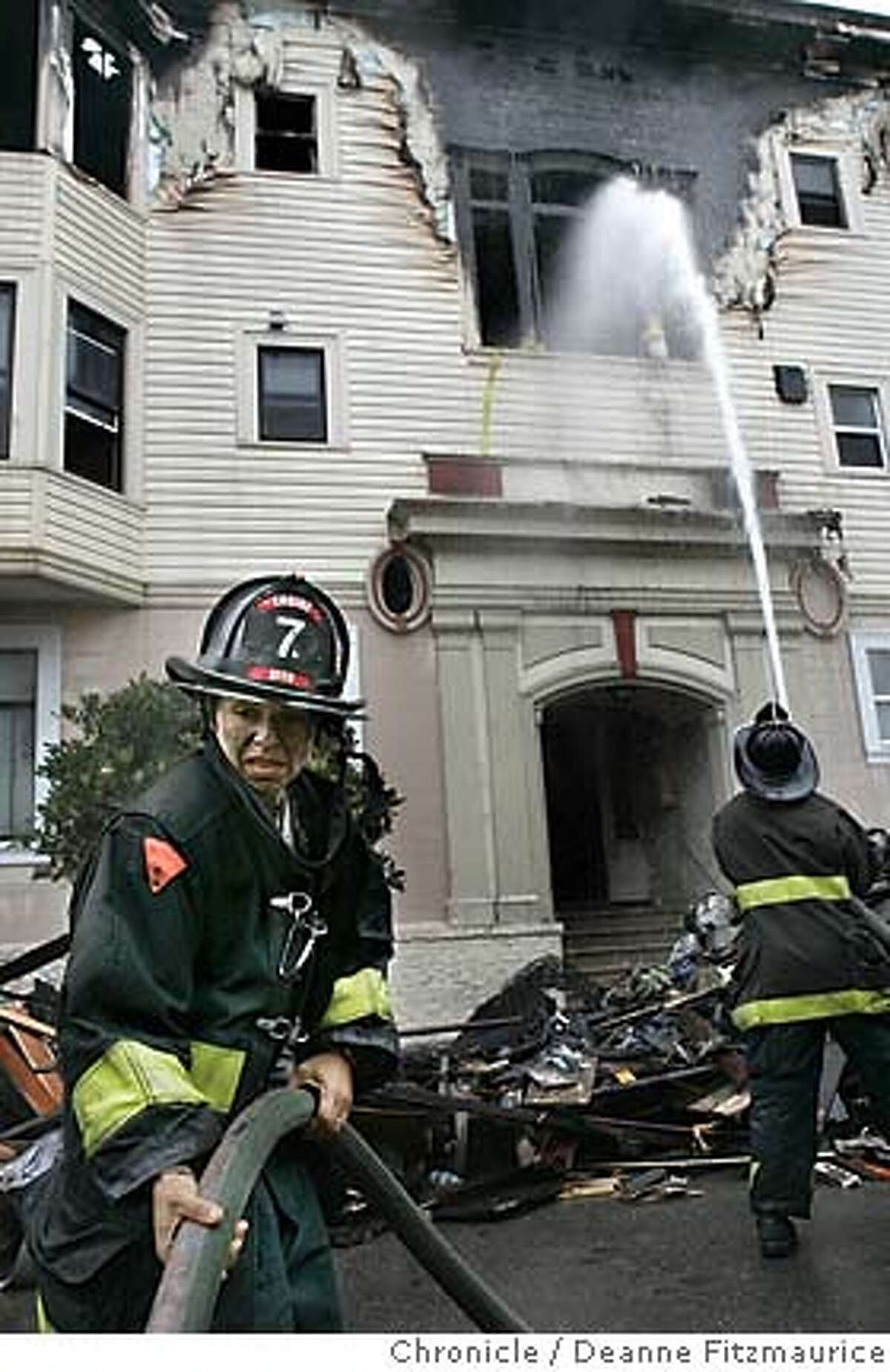 Firefighter Sadie Magaly helps with the hose. Firefighters are on the scene after an early morning fire on Capp Street in the Mission District. Deanne Fitzmaurice / San Francisco Chronicle