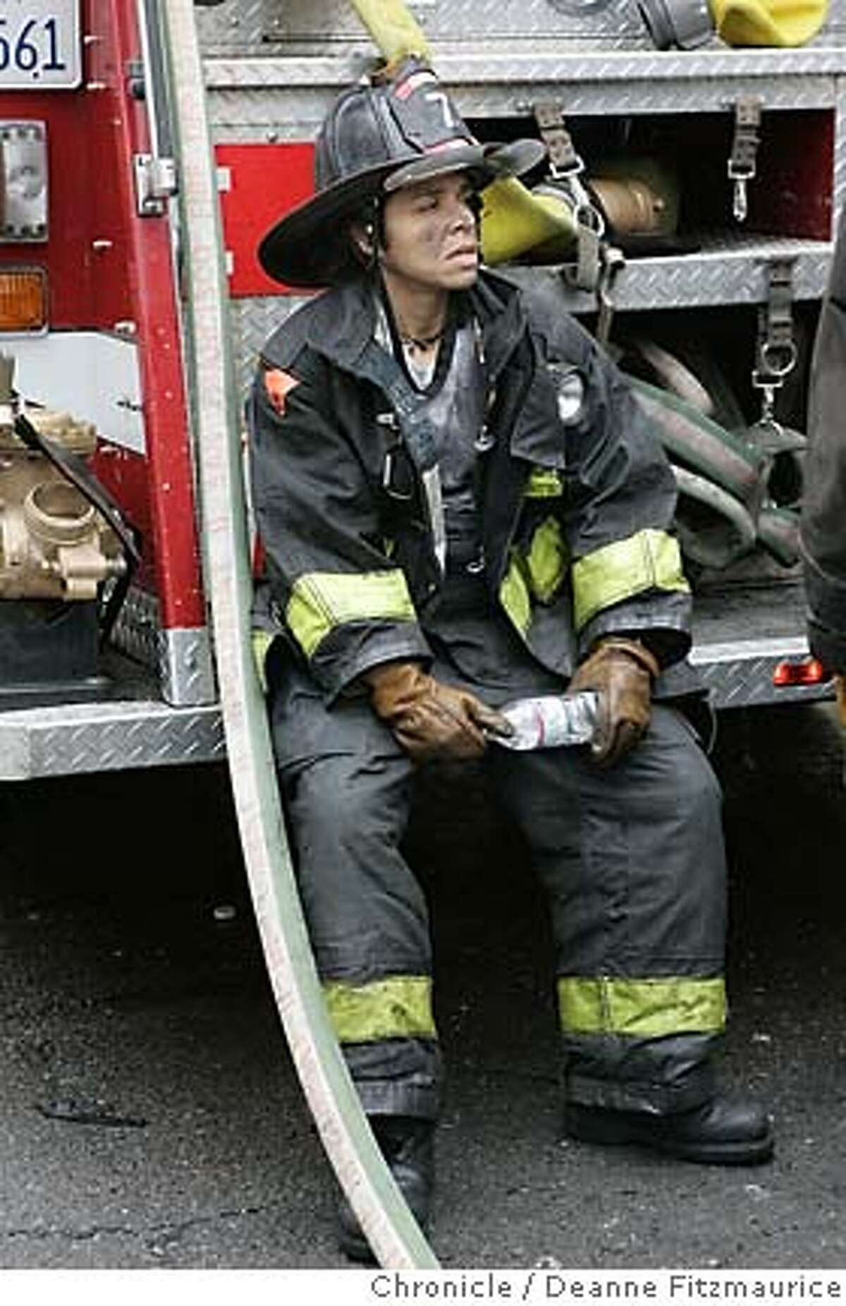 Firefighter Sadie Magaly takes a rest after fighting the fire. Firefighters are on the scene after an early morning fire on Capp Street in the Mission District. Deanne Fitzmaurice / San Francisco Chronicle