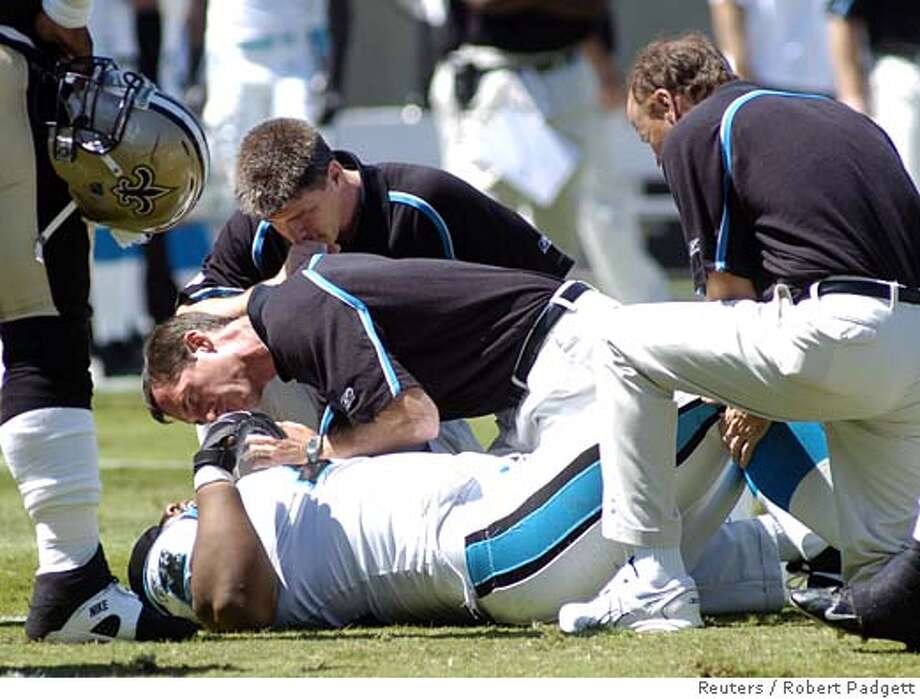 Carolina Panthers staff talk to defensive tackle Kris Jenkins, who was helped from the field during NFL action against the New Orleans Saints, at Charlotte, September 11, 2005. Jenkins returned to action in the second half. REUTERS/Robert Padgett 0 Photo: ROBERT PADGETT