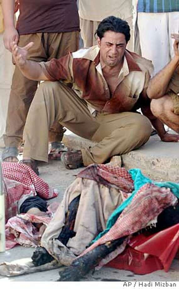 An Iraqi man reacts as he sits next to the bodies of victims, outside the Kazimiyah hospital, following an explosion in Baghdad, Wednesday, Sept. 14, 2005. At least 73 people were killed and 162 wounded early Wednesday when a suicide bomber detonated his vehicle near a group of construction workers in north Baghdad, police said. (AP Photo/Hadi Mizban) Photo: HADI MIZBAN