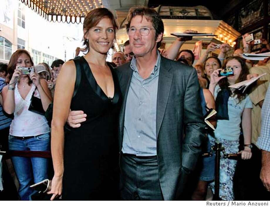 "Actor Richard Gere (R) and his wife Carey Lowell at a special screening of the ""Bee Season"" at the 30th Toronto International Film Festival in Toronto September 11, 2005. REUTERS/Mario Anzuoni 0 Photo: MARIO ANZUONI"