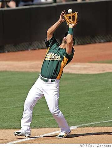 Oakland Athletics third baseman Eric Chavez makes a catch for an out on a fly ball hit by Los Angeles Angels' Erick Aybar on the left field line in the fourth inning of a split-squad spring training baseball game Sunday, March 18, 2007, in Phoenix.(AP Photo/Paul Connors) Photo: Paul Connors