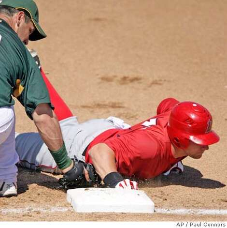 Los Angeles Angels' Reggie Willits, right, dives safely back to first just before Oakland Athletics first baseman Erubiel Durazo, left, gets the tag attempt down in the fourth inning of a split-squad spring training baseball game Sunday, March 18, 2007, in Phoenix. (AP Photo/Paul Connors) Photo: Paul Connors