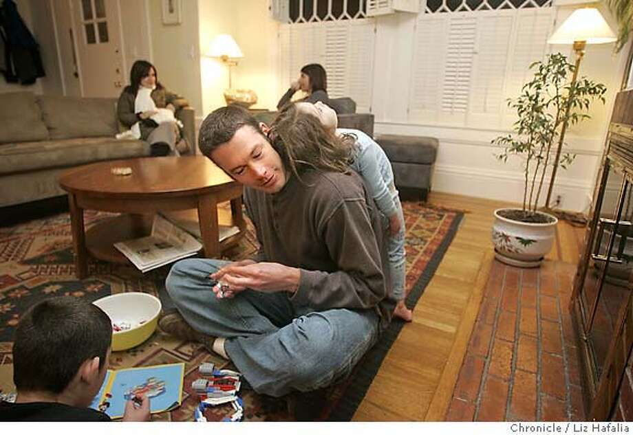 �TRANS12SOL_PH032_LH.jpg Greg Amundson (middle) playing with his daughter Dorri Amundson (on his back), 4 years old, and his son Taghi Amundson (left), 6 years old, in the living room. Mitra Modarressi (back, right) is talking with her friend, Krissy Lewis (back, left), who is babysitting tonight. Mitra Modarressi and Greg Amundson have installed solar panels on their roof. cq--Greg Amundson, Dorri Amundson, Taghi Amundson, Mitra Modarressi, Krissy Lewis Photographed by Liz Hafalia in San Francisco on 2/8/07. Photo: Liz Hafalia