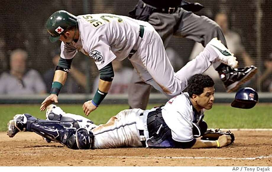 Oakland Athletics Nick Swisher jumps over Cleveland Indians catcher Victor Martinez after scoring on a wild pitch by Indians pitcher Kevin Millwood in the fifth inning Tuesday, Sept. 13, 2005 in Cleveland. (AP Photo/Tony Dejak) Photo: TONY DEJAK