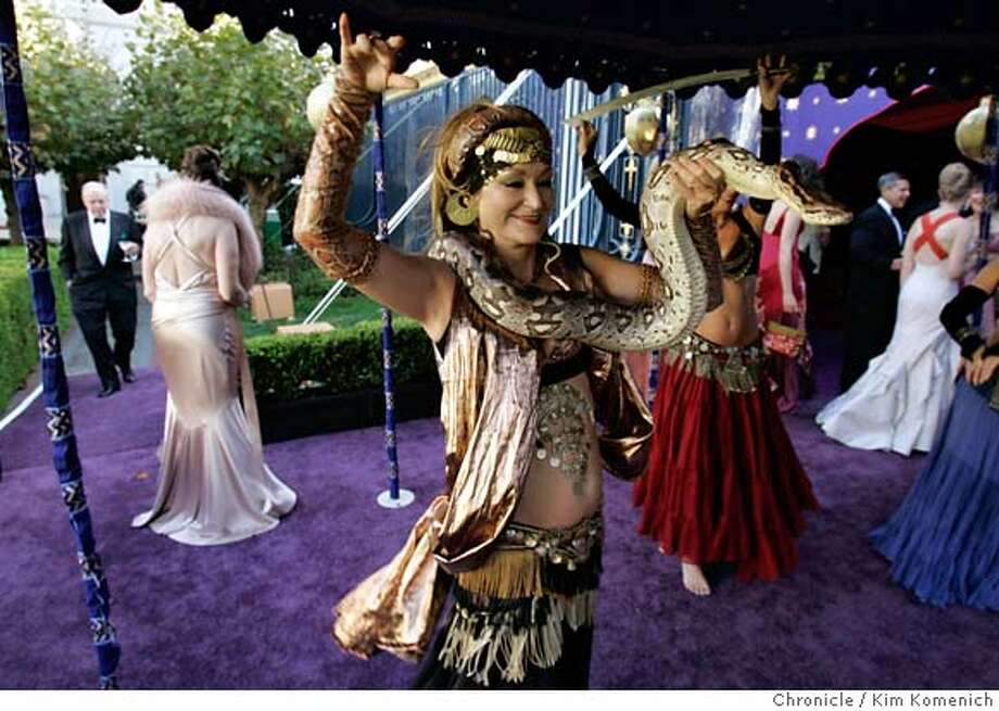 "SFOPERA_STYLE120130_kk.JPG  Asia, owner of the Asia Belly Dance Troupe, performs with ""Rajah"" the boa constrictor as Ann Caen stands with a feather boa in the background.  The San Francisco Opera's 83rd opening night gala. NOTE: This shoot (for Bigelow) was done simultaneously with ROSENBURG12 (for Zinko.) We follow operagoers through the parties before the Opera' s performance of ""Italian Girl in Algiers."" We also shadow outgoing Opera General Director during the hours before the opening.  San Francisco Chronicle Photo by Kim Komenich  9/10/05 Photo: Kim Komenich"