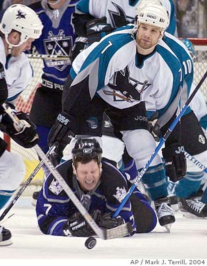 Los Angeles Kings' Derek Armstrong of Canada falls to the ice in front of San Jose Sharks' Brad Stuart of Canada as the Sahrk's Nils Ekman of Sweden takes the puck during the third period, Thursday night, March 18, 2004, in Los Angeles. The Sharks won the game 5-3. (AP Photo/Mark J. Terrill) Photo: MARK J. TERRILL