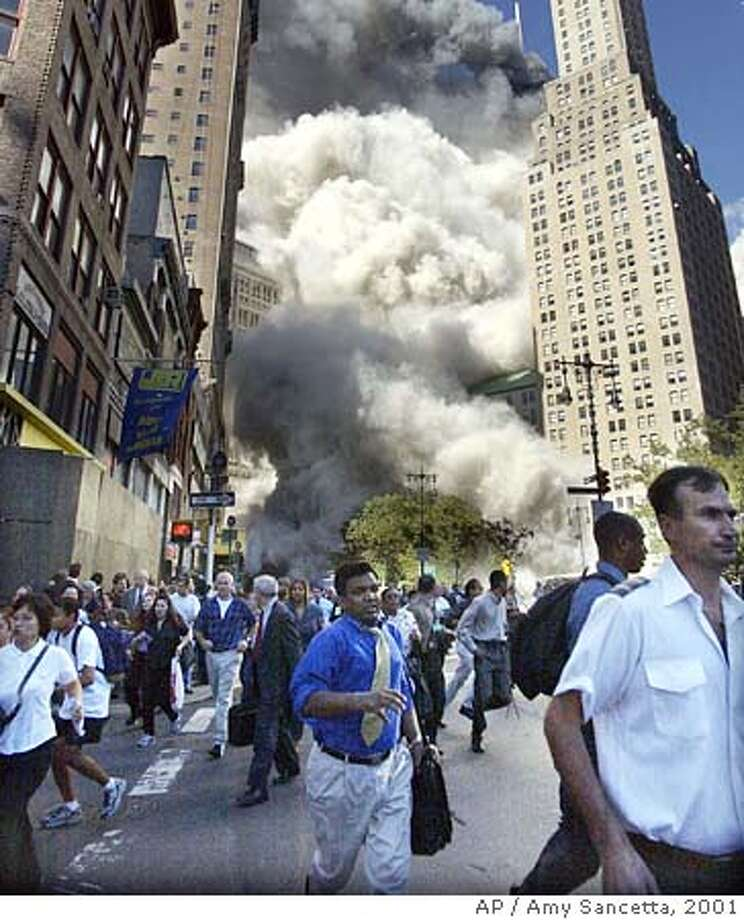 ** FILE ** In a file photo pedestrians flee the area of the World Trade Center as the center's south tower collapses following a terrorist attack Tuesday, Sept. 11, 2001. In the oil-rich Arab countries of the Gulf, Sept. 11 is increasingly being seen as the event that kicked off a galloping economic boom, when Arabs divested from America and reinvested at home. (AP Photo/Amy Sancetta) Photo: AMY SANCETTA