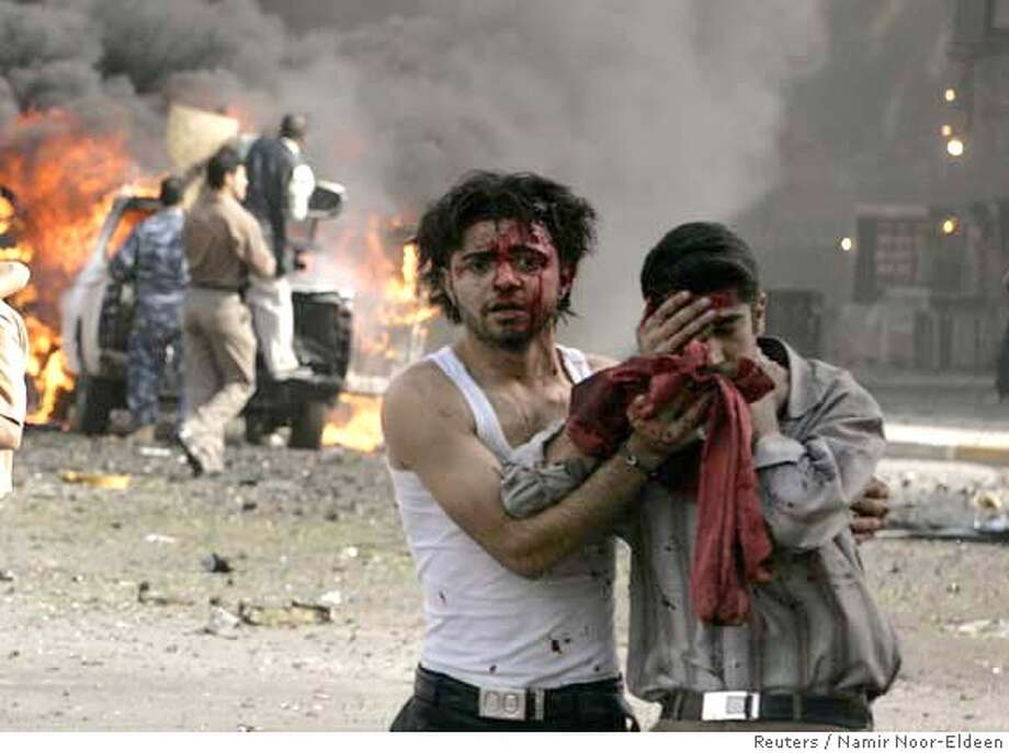 Victims walks away after a car bomb attack in Baghdad March 15, 2007. A car bomb targeting a joint Iraqi army and police checkpoint exploded in central Baghdad on Thursday, causing an unknown number of casualties, police said. REUTERS/Namir Noor-Eldeen (IRAQ) 0 Photo: NAMIR NOOR-ELDEEN
