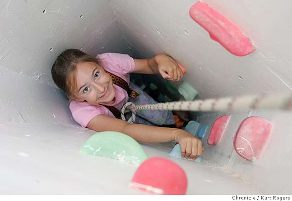 Annaka Olson climbs up the shaft that goes from the basement to the attic. This house in Mountain View has a small backyard, so the parents built slides and secret passages within the house that the children can use for play. There's a slide from the first floor to the basement, rock climbing walls in the basement, a secret passage to the attic from the childrens' bedroom, a shaft from the basement to the attic and other neat features. 5/11/05 in Mountan View,CA. KURT ROGERS/THE CHRONICLE