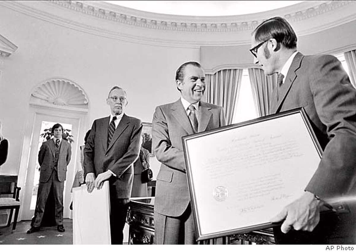 U.S. President Richard Nixon presents a framed commission to William H. Rehnquist, right, after giving a similar one to Lewis F. Powell Jr., left, at a White House ceremony in Washington, D.C., Wednesday, Dec. 22, 1971. Both Powell and Rehnquist are commissioned as Associate Justices of the Supreme Court and will take their oath Jan. 7. (AP Photo)