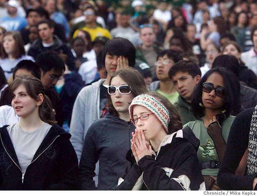 Elizabeth Beatty, 15, of San Bruno, CA prays as she listens to the bands
