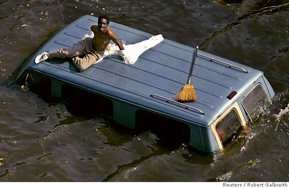 A man sits on the top of a vehicle as he waits to be rescued by the U.S. Coast Guard from the flooded streets of New Orleans in the aftermath of Hurricane Katrina in New Orleans, Louisiana September 4, 2005. Residents continue to be rescued from their homes and the streets of the flood ravaged city. REUTERS/Robert Galbraith 0 Photo: ROBERT GALBRAITH
