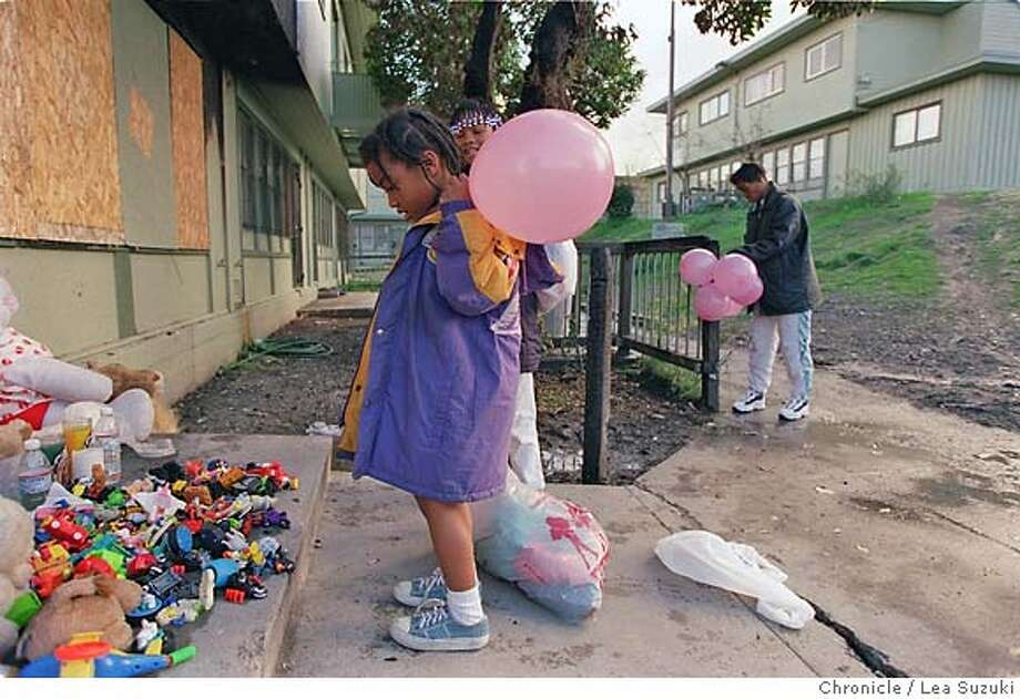 Mourners contribute to a makeshift memorial for Delores Evans and five children, who perished in a San Francisco public housing fire. Chronicle photo, 1997, by Lea Suzuki