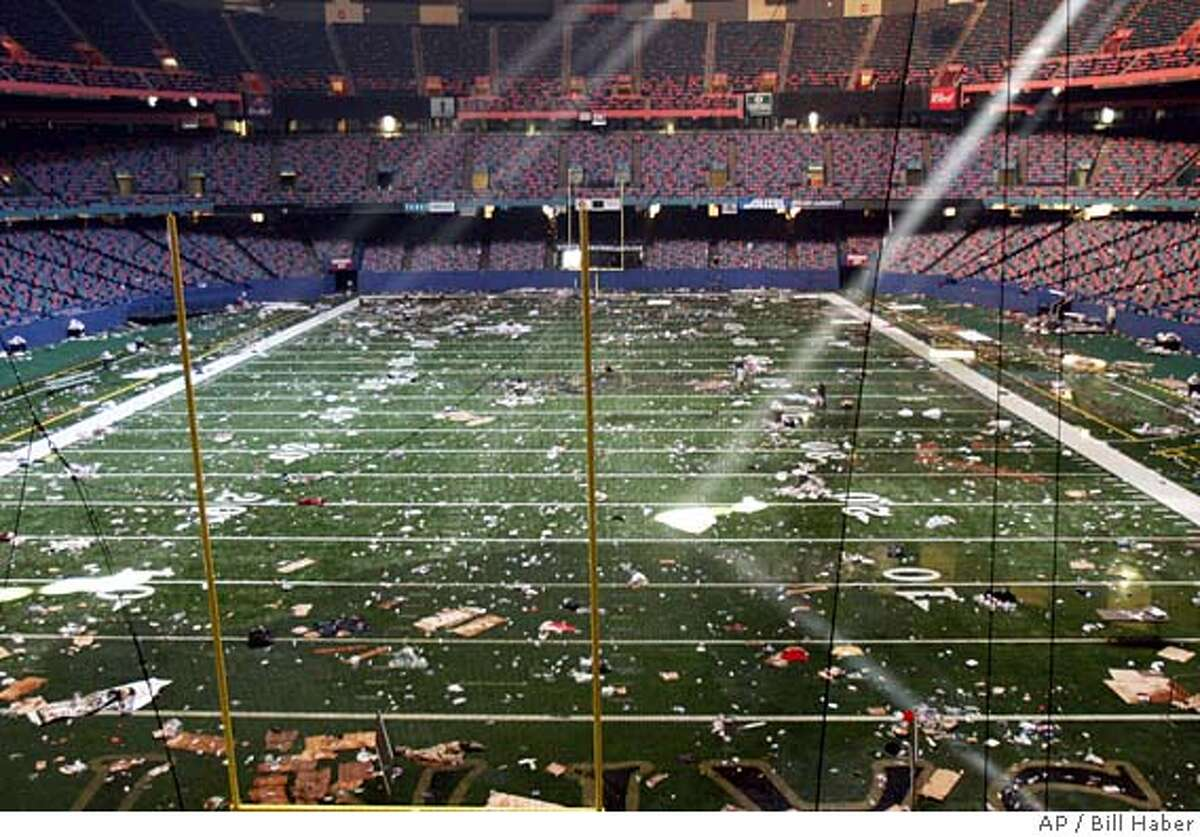 Huge shafts of light strike the playing field of the Louisiana Superdome in New Orleans on Friday, Sept. 2, 2005. The dome is littered with debris after serving as a shelter for victims from Hurricane Katrina. The light is filtering in through holes in the roof. A huge military presence has arrived in the city, restoring order and bringing with them food and water to feed the thousands of victims of Hurricane Katrina. (AP Photo/Bill Haber)