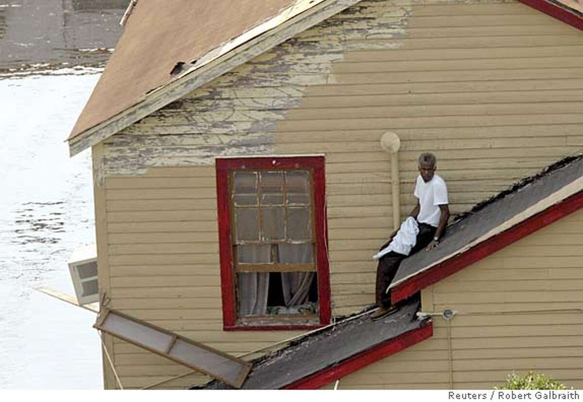 A man waits to be rescued from the roof of a house as flood waters continue to rise in the aftermath of Hurricane Katrina in New Orleans, Louisiana September 2, 2005. U.S. commercial airlines plan to ferry more than 25,000 New Orleans residents displaced by Hurricane Katrina from the city to safer locations, the airline industry and the U.S. government said on Friday. REUTERS/Robert Galbraith 0
