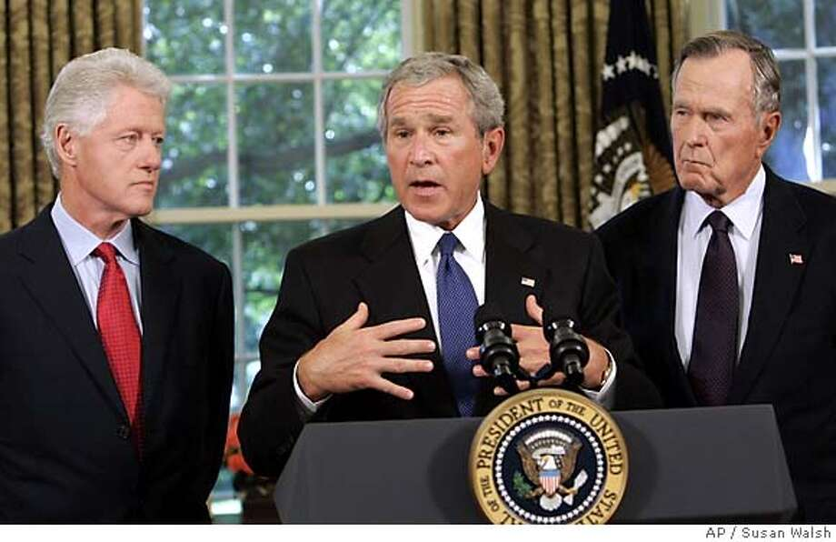 President Bush meets with former President George H.W. Bush, right, and former President Bill Clinton, right, in the Oval Office of the White House, Thursday, Sept. 1, 2005. Bush, who will tour the hurricane-devastated Gulf Coast region on Friday, has asked his father, former President George H.W. Bush, and former President Bill Clinton to lead a private fund-raising campaign for victims as they did for last year's Asian tsunami. (AP Photo/Susan Walsh) Photo: SUSAN WALSH