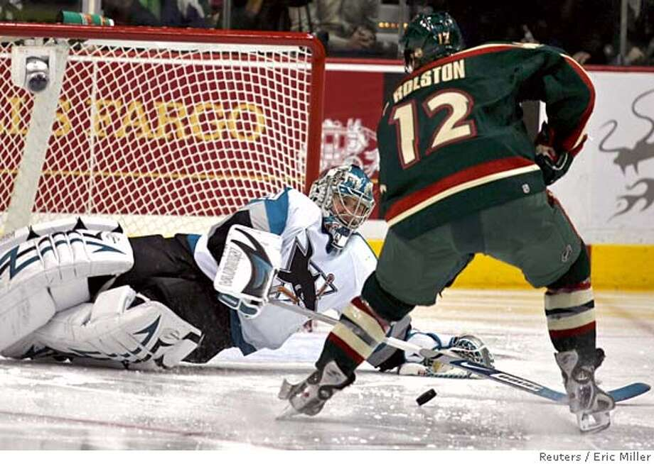 San Jose Sharks goalie Evgeni Nabokov dives to successfully stop a break-away by Minnesota Wild left wing Brian Rolston (12) with his stick during the second period of their NHL game in St. Paul, Minnesota, March 6, 2007. REUTERS/Eric Miller (UNITED STATES) Photo: ERIC MILLER