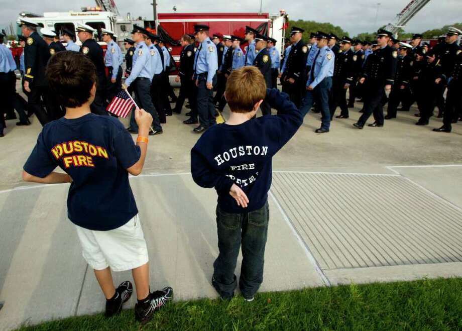 "Keegan Ross, left, and Camden Ross salute a procession of firefighters during a memorial service for Houston Fire Department Senior Capt. Thomas. W. ""Bill"" Dillion at Second Baptist Church Monday, March 19, 2012, in Houston. The 22-year HFD veteran died in the line of duty on March 14. Photo: Brett Coomer, Houston Chronicle / © 2012 Houston Chronicle"