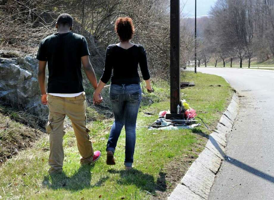 Shaun Hendricks, 16, left and Marilyn Valerio, 18, friends of Christopher Reyes, walk to the makeshift memorial at the spot where Reyes died in a car accident Sunday night, Monday, March 19, 2012. Photo: Carol Kaliff