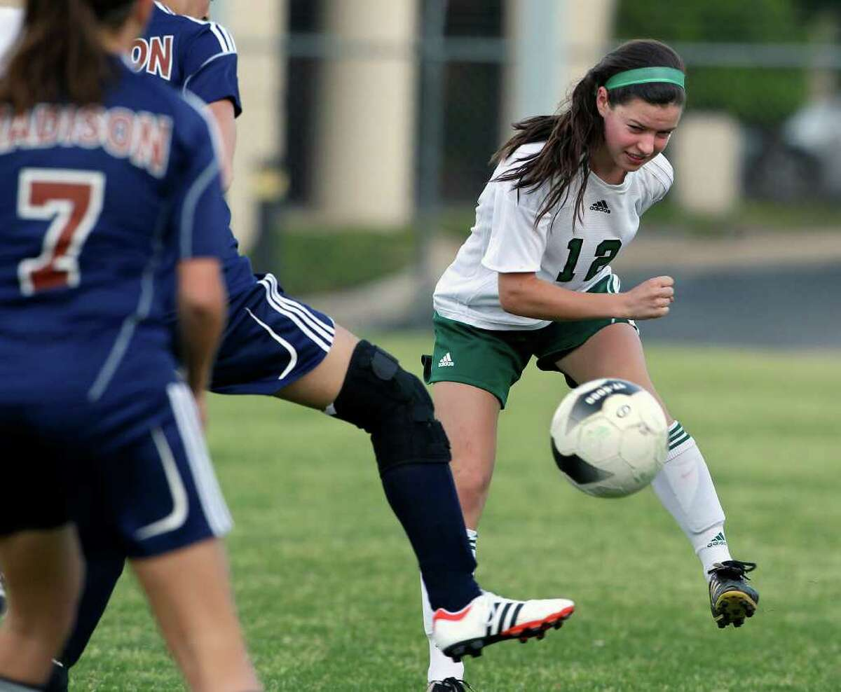 Reagan's Christine Carrera works a pass around Madison's defense as Reagan in the Rattlers' 7-0 win March 13 at Blossom Soccer Stadium. The win was the 500th career victory for Reagan girls soccer coach Frankie Whitlock.