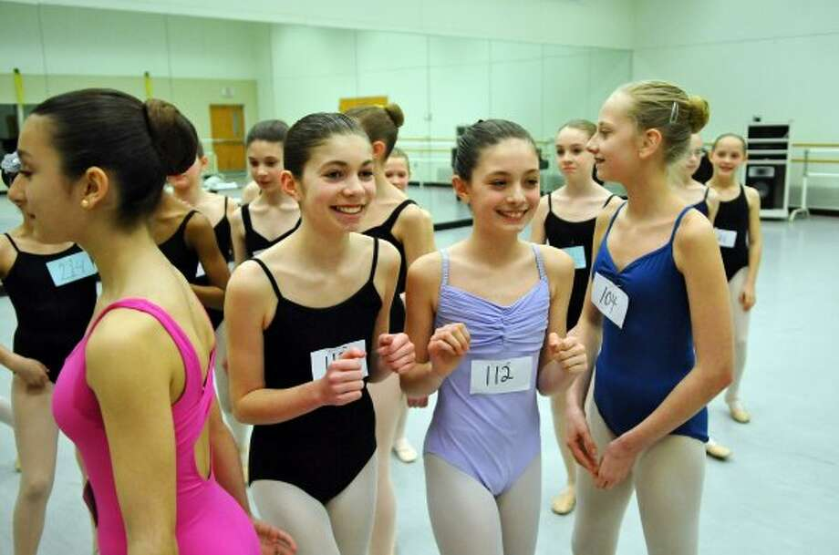 Alexandra Merrill, second from right (wearing #112) and Grace Stewart, second from left, both 12 of Niskayuna, after being told that they had been chosen for an audition for children for the upcoming New York City Ballet performances of Firebird and Romeo + Juliet this summer at SPAC, as the National Museum of Dance on Sunday March 18, 2012 in Saratoga Springs, N.Y. About 200 young dancers tried out. All of the girls shown were among those chosen for parts in the ballet performances.  (Philip Kamrass / Times Union ) (Albany Times Union)