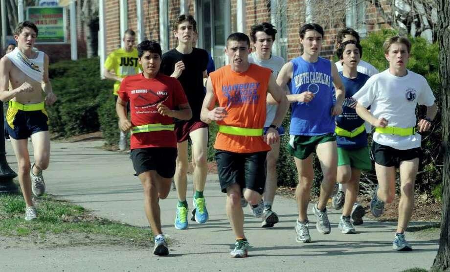 The Danbury High School cross country team takes a run down Main Street in Danbury Monday, March 19, 2012. Photo: Carol Kaliff / The News-Times