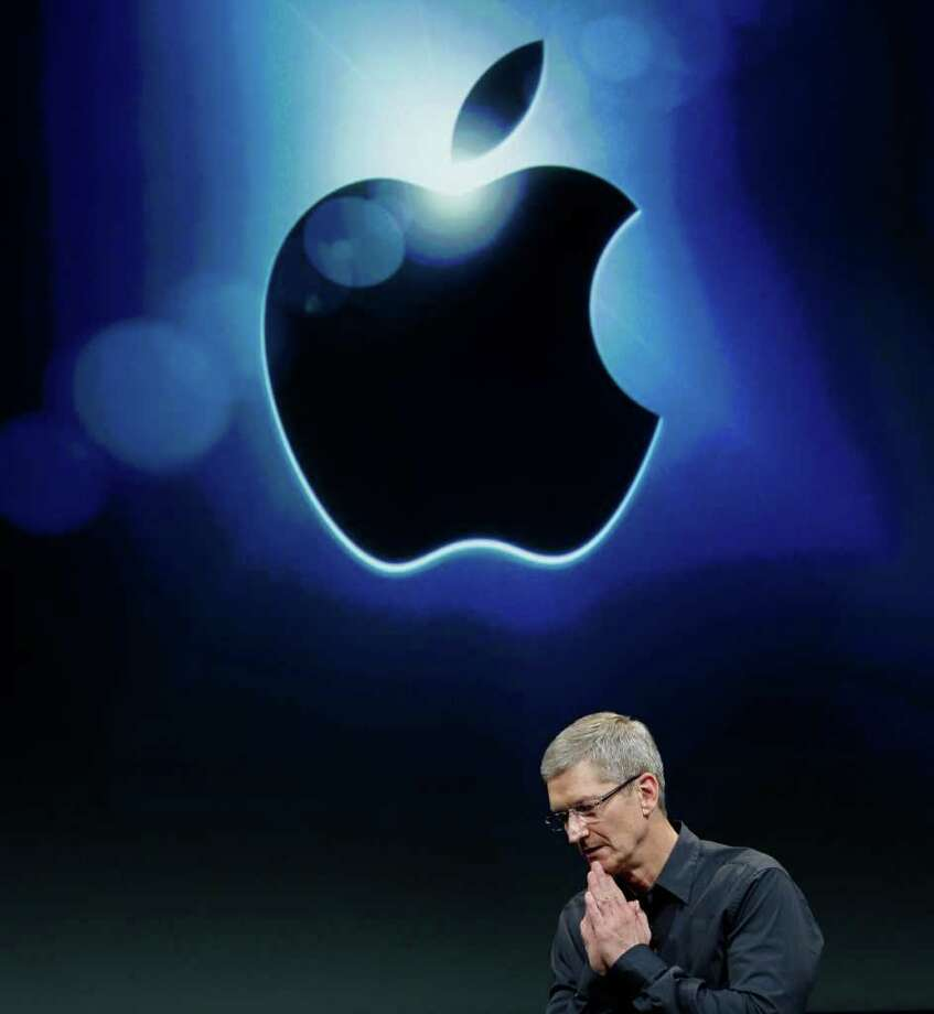FILE - In this Oct. 4, 2011 file photo, Apple CEO Tim Cook gestures during the introduction of the iPhone 4S, at Apple headquarters in Cupertino, Calif. Apple Inc. said it will announce the outcome of its internal discussion concerning its enormous cash balance on Monday morning March 19, 2012. (AP Photo/Paul Sakuma, File) Photo: Paul Sakuma / AP2011