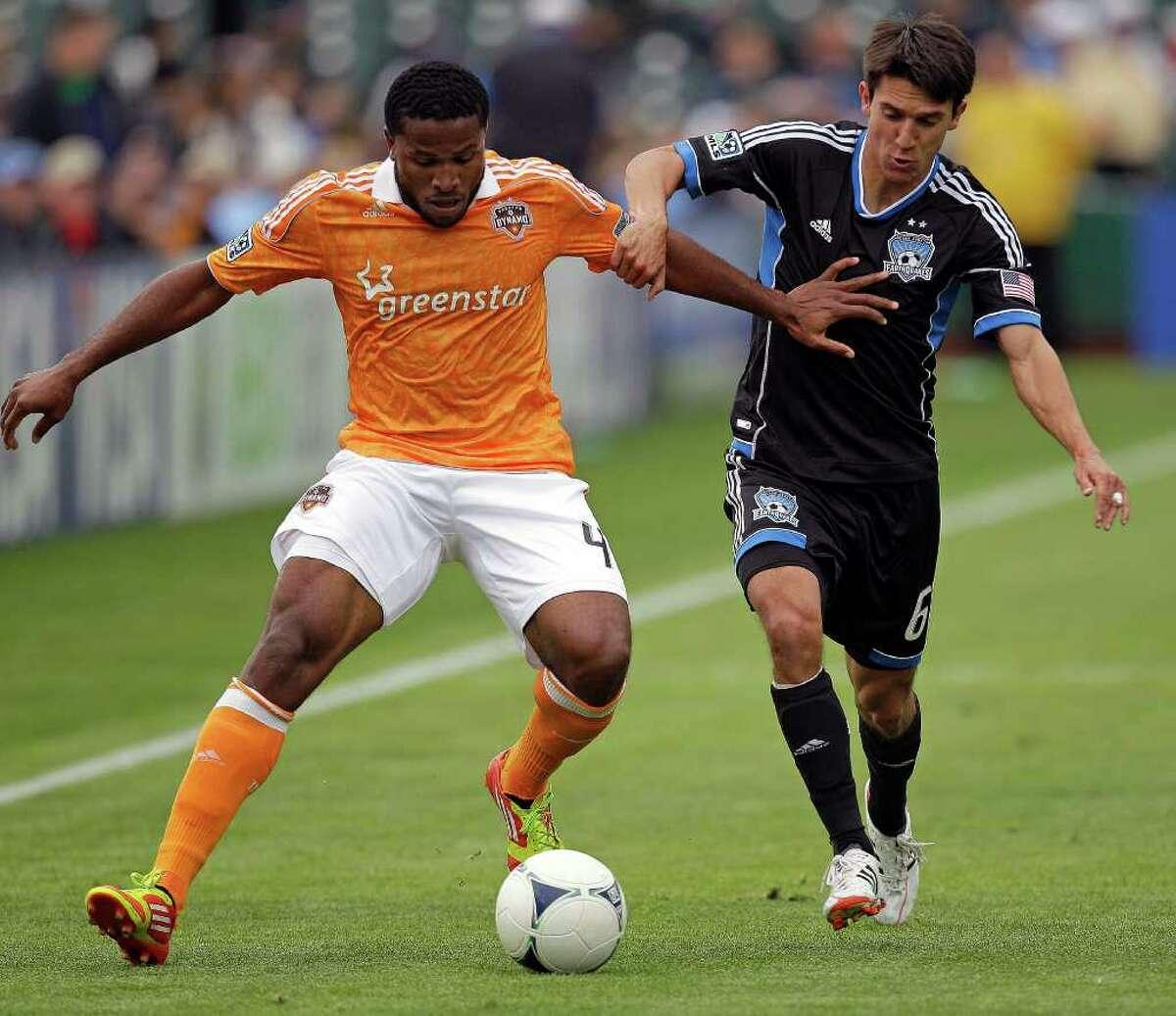 Dynamo defender Jermaine Taylor, left, battles the Earthquakes' Shea Salinas.
