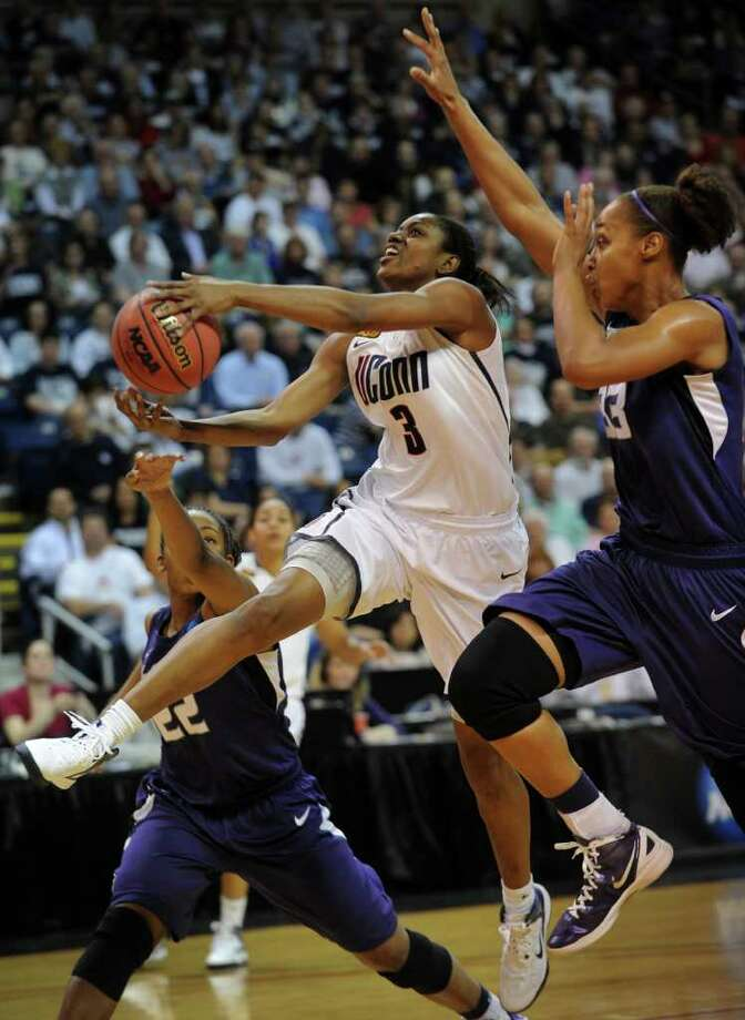UConn's Tiffany Hayes streaks to the basket between Kansas State defenders Mariah White, left, and Jalana Childs during the first half of their matchup in the second round of the NCAA women's basketball tournament at the Webster Bank Arena in Bridgeport on Monday, March 19, 2012. Photo: Brian A. Pounds / Connecticut Post