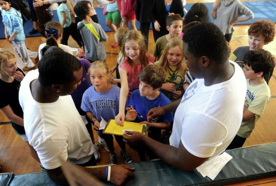Football players Alex Joseph Vladimir Ducasse sign autographs for Lucy Saleeby, 11 and Zach Caruso, 10, during a fundraising kick off for the Be Like Brit Foundation at North Mianus School Monday, March 19, 2012. The Foundation will help raise funds to build a Haitian orphange. Photo: Helen Neafsey / Greenwich Time