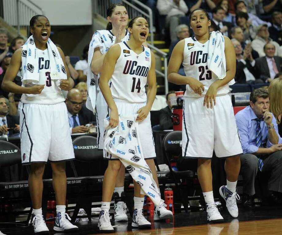 From left; UConn players Tiffany Hayes, Stefanie Dolson, Bria Hartley, and Kaleena Mosqueda-Lewis cheer on their teammates in the final minutes of their victory over Kansas State in the second round of the NCAA women's basketball tournament at the Webster Bank Arena in Bridgeport on Monday, March 19, 2012. At right is coach Geno Auriemma. Photo: Brian A. Pounds / Connecticut Post