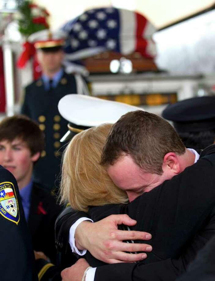 "David Dillion, son of Houston Fire Department Senior Capt. Thomas W. ""Bill"" Dillion, is embraced by a mourner during a memorial service for the fallen firefighter at Second Baptist Church Monday in Houston. Photo: Brett Coomer / © 2012 Houston Chronicle"